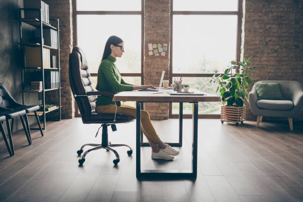 Full length profile photo of busy brunette business lady resourceful person notebook table modern user sit boss chair wear specs green turtleneck yellow pants modern interior office stock photo
