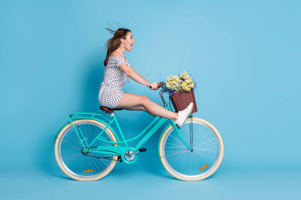 Full length profile photo of crazy girl drive bike raise legs wear dotted short dress footwear isolated blue color background stock photo