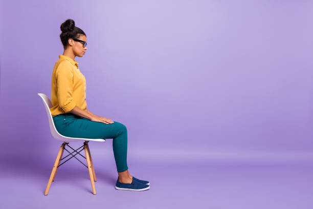 pełna długość zdjęcie profilowe dość ciemnej skóry pani na krześle wyglądają pusta przestrzeń słuchać pracodawca pytanie wywiad nosić specyfikacje żółte spodnie koszuli izolowane fioletowy kolor tła - krzesło zdjęcia i obrazy z banku zdjęć