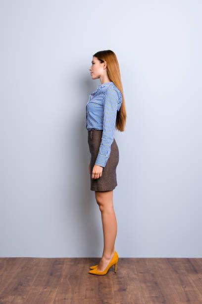 voller länge profilbildnis ernst junge dame in strenge formelle kleidung, stehen immer noch auf hellem hintergrund in pumpe schuhe - lange gestreifte röcke stock-fotos und bilder