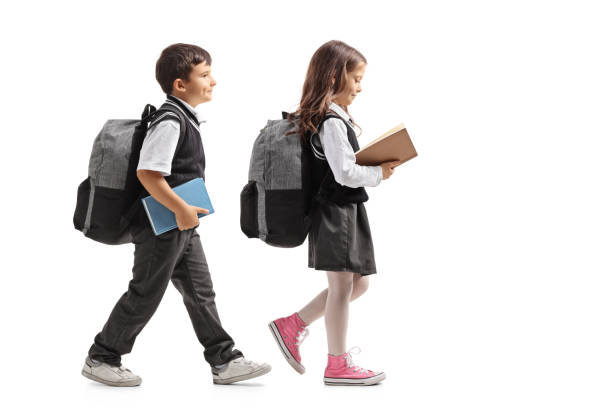 full length profile shot a schoolboy and a schoolgirl with backpacks and books walking - uniform stock photos and pictures