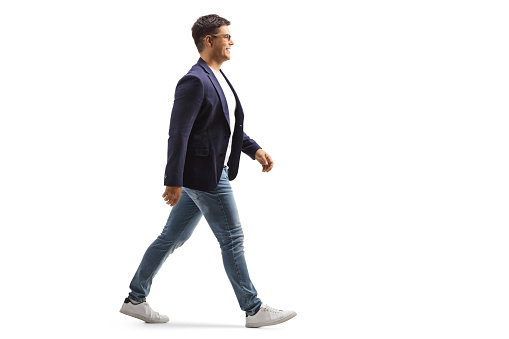 Full length profile shot of a smiling young man in jeans and suit walking isolated on white background