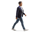 istock Full length profile shot of a smiling young man in jeans and suit walking 1280221874
