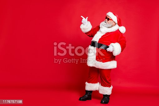 istock Full length profile side photo of charming santa claus in eyewear eyeglasses showing promo wearing bright costume belt isolated over red background 1176757158