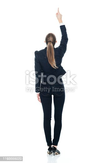 Full length / rear view / back / looking up / front view / looking at camera / one person of 20-29 years old adult beautiful brown hair / ponytail caucasian female / young women business person / businesswoman standing wearing business casual / smart casual / blazer - jacket / jacket / jeans / pants / button down shirt / shirt and high heels who is pointing with hand by side