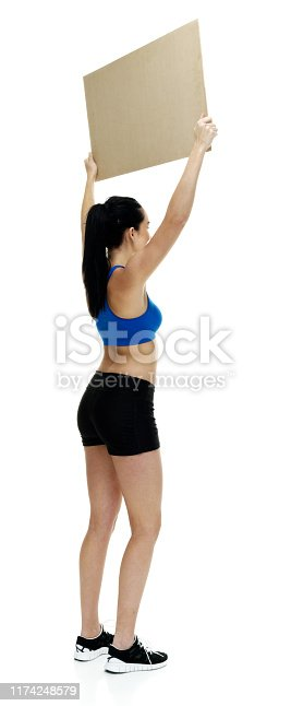 istock Full length / rear view / back of 18-19 years old adult beautiful black hair / long hair / ponytail caucasian female / young women athlete / sportsperson standing in front of white background who is smiling / happy / cheerful who is showing 1174248579