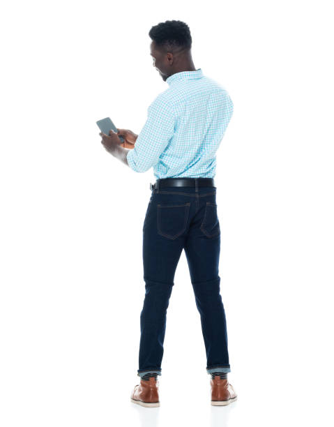 Full length / rear view / back / one man only / one person of 20-29 years old adult handsome people curly hair / black hair african ethnicity / african-american ethnicity / generation z male / young men standing and holding mobile phone stock photo