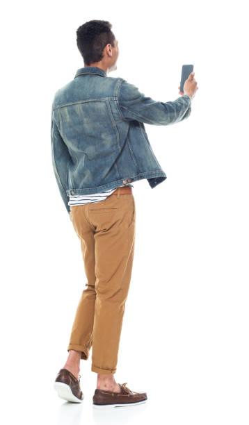 Volle Länge / Rückansicht von 20-29 Jahre alt erwachsene stattliche Menschen / große Person afrikanische Ethnizität / african-american ethity männlich / junge Männer stehen vor weißem Hintergrund tragen Bootsschuh / Jeansjacke / coole Haltung – Foto
