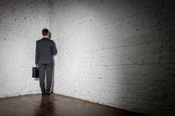 Full length rear view of businessman standing in corner at office Full length rear view of businessman standing in corner at office punishment stock pictures, royalty-free photos & images