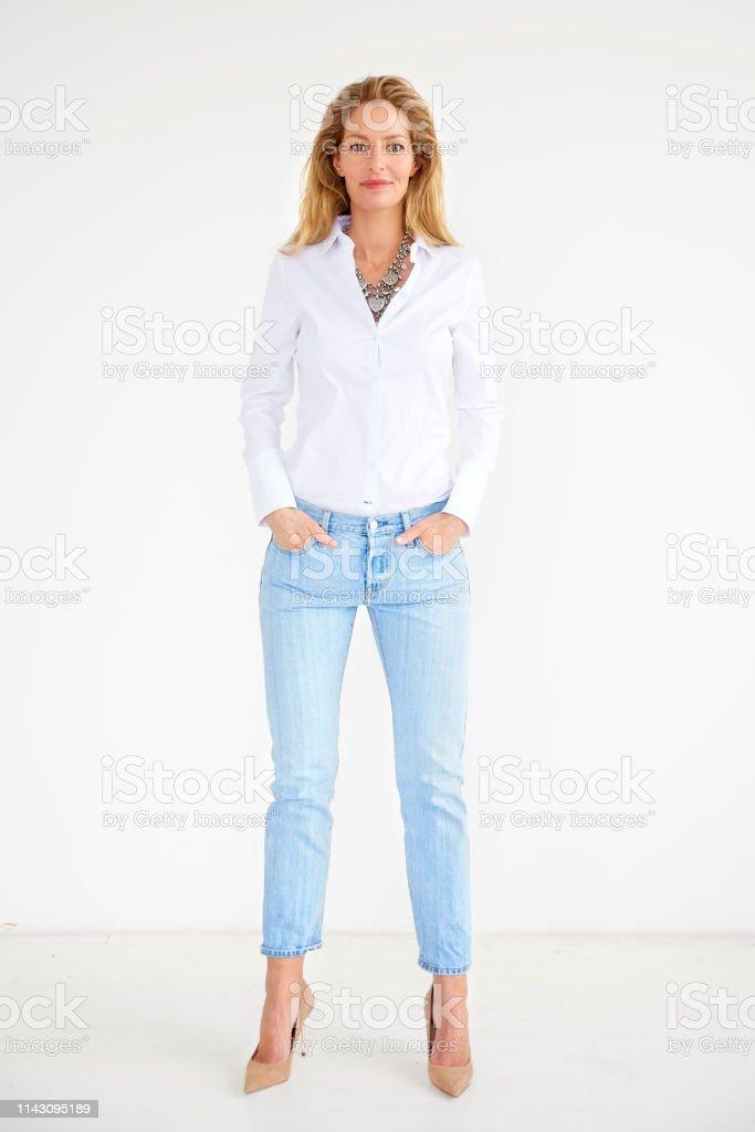 Pleine longueur de tir de femme âgée moyenne attirante portant des vêtements occasionnels tout en restant à l'arrière-plan isolé - Photo