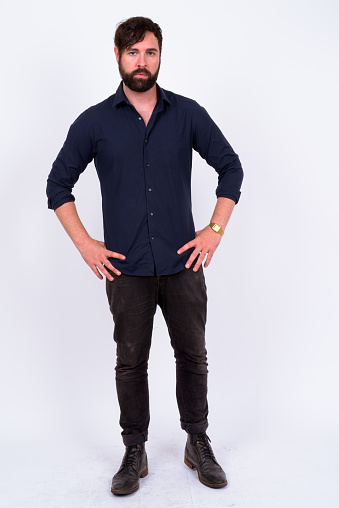 931173966 istock photo Full Length Shot Of Handsome Bearded Man With Blue Eyes And Tattoos Standing Against White Background 899698998