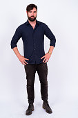 istock Full Length Shot Of Handsome Bearded Man With Blue Eyes And Tattoos Standing Against White Background 899698998