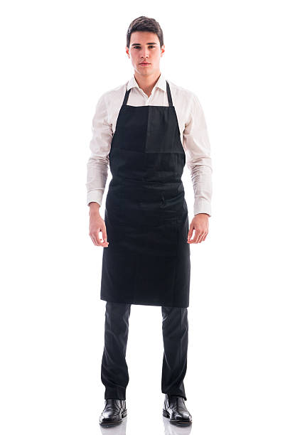 full length shot of young chef or waiter posing isolated - apron stock pictures, royalty-free photos & images
