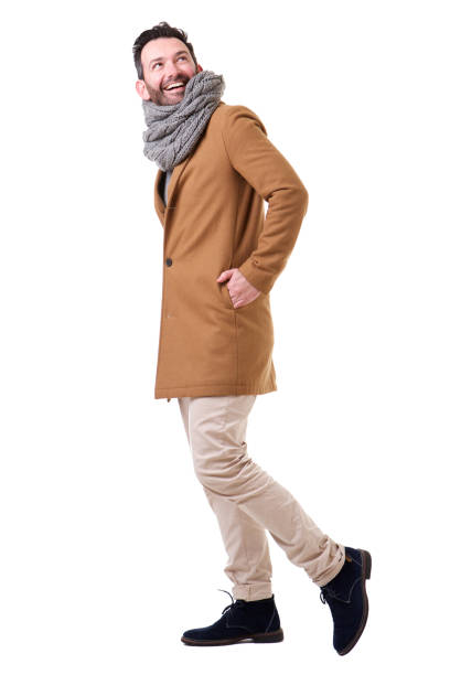 Full length side of man walking with coat and scarf against white background Full length side portrait of man walking with coat and scarf against white background warm clothing stock pictures, royalty-free photos & images