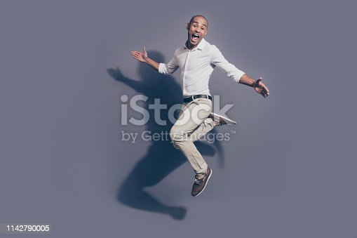 925466128 istock photo Full length side profile body size photo amazing dark skin he him his macho jumping high great mood childish playful crazy fooling around wear white shirt pastel pants isolated grey background 1142790005