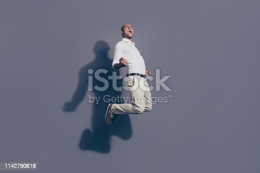 925466128 istock photo Full length side profile body size photo amazing yelling dark skin he him his model macho handsome jump high true fan goal cheerleader football wear white shirt pastel pants isolated grey background 1142790618