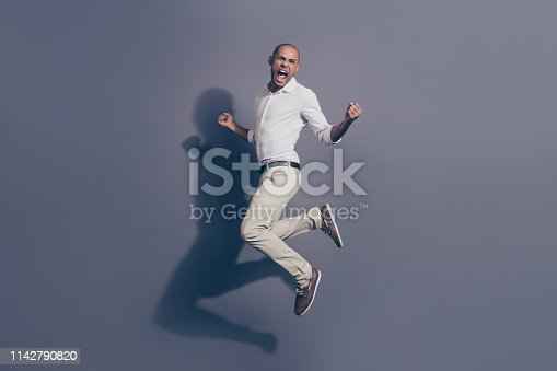925466128 istock photo Full length side profile body size photo amazing yelling dark skin he him his macho jumping great mood cheerleader football baseball basketball wear white shirt pastel pants isolated grey background 1142790820