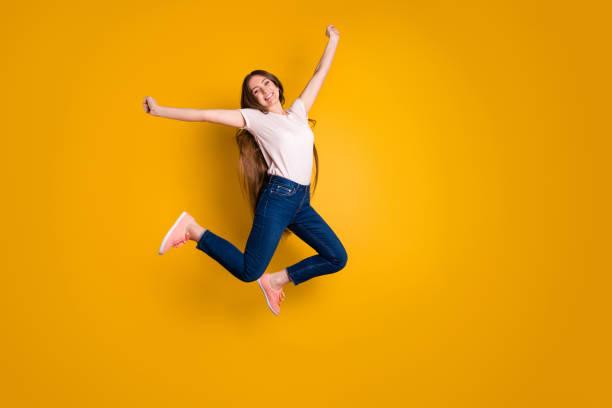 volle länge seite profil körpergröße foto schön erstaunlich sie ihre stilvolle dame sehr lange haar flug springen hochgespreizte hände arme tragen lässige jeans jeans rosa schuhe t-shirt isoliert gelb hintergrund - damen jeans sale stock-fotos und bilder