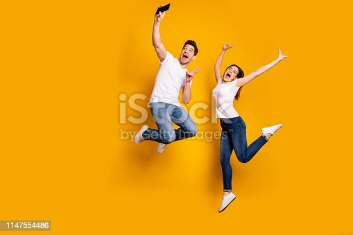 Full length side profile body size photo funky funny crazy people she her he him his guy lady jump high show v-sign make take selfies wear casual jeans denim white t-shirts isolated yellow background.