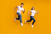 Full length side profile body size photo funky funny she her he him his guy lady jump high hurry shopping black friday low prices wear casual jeans denim white t-shirts isolated yellow background.