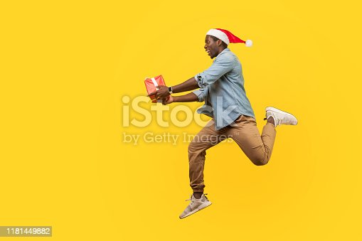 925466128 istock photo Full length side view of joyous handsome young man in santa hat and casual denim shirt jumping or running with christmas gift box, hurry for sales. 1181449882