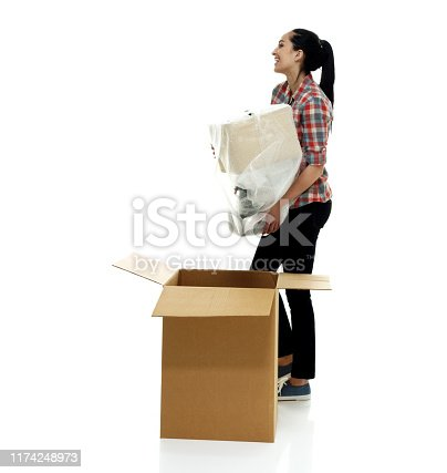 Full length / side view / profile view of 18-19 years old adult beautiful black hair / long hair / ponytail caucasian female / young women standing in front of white background wearing jeans / pants / lumberjack shirt / plaid shirt / button down shirt / shirt / canvas shoe who is smiling / happy / cheerful / cool attitude who is picking up / packing / unpacking / moving house / relocation and holding box - container / electric lamp