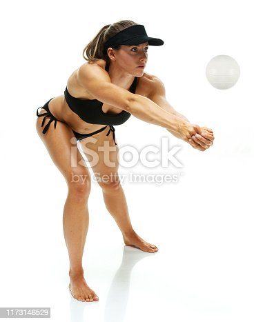 Full length / side view / profile view of 20-29 years old adult beautiful brown hair / long hair caucasian female / young women athlete standing in front of white background wearing sports bra / bra / bikini / swimwear / sun visor / cap - hat / hat who is serious / confidence / concentration who is barefoot / hitting and holding volleyball - ball / using sports ball / volleyball - sport / sport
