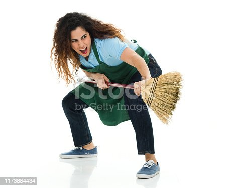 Full length / side view / profile view of 30-39 years old adult beautiful puerto rican ethnicity / latin american and hispanic ethnicity female / young women / one young woman only barista / with part-time job / caretaker / cleaner / manual worker in front of white background wearing jeans / apron / t-shirt / shirt / canvas shoe who is serious / aggression / angry / cool attitude and showing fist who is working / in fighting stance / fighting / punching / violence / sweeping / cleaning / doing chores and holding broom / swinging / hygiene