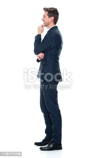 Full length / side view / profile view / one man only / one person of 20-29 years old adult handsome people brown hair / with beard caucasian male / young men manager / businessman / business person standing wearing businesswear / business casual / smart casual / open collar / button down shirt / shirt / fully unbuttoned / a suit who is smiling / happy / cheerful / laughing / contemplating / uncertainty / asking