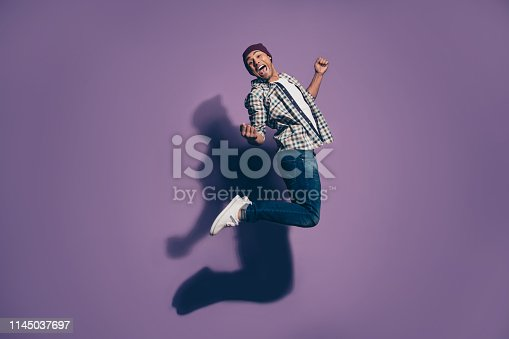 925466128 istock photo Full length size body photo of crazy funky cool carefree flying triumphing wearing denim outfit millennial person raising hands fists isolated violet background 1145037697