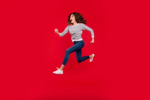 voller länge größe körper foto von fliegen hoch charmante sie ihr mädchen schnell laufen zum einkaufszentrum verkauf tragen weiße lässige gestreiften pullover denim-jeans auf roten lebendige hellen hintergrund speichern - druck jeans stock-fotos und bilder