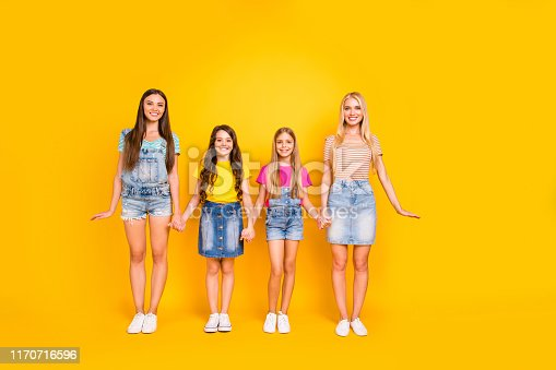 istock Full length size body photo of four nice positive glad charming ladies with beaming smile holding hands wearing denim clothes t-shirts isolated shiny vivid background 1170716596