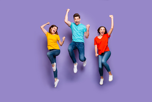Full length size body photo of three crazy funky carefree buddies teamwork, company raising fists up isolated violet background