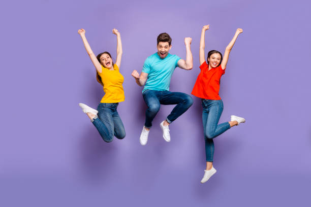 Full length size body photo of three funny funky ecstatic excited delightful buddies having fun on weekend isolated violet background stock photo