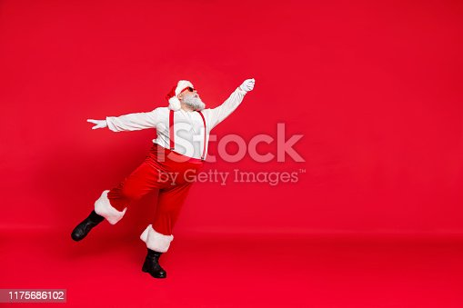 istock Full length size photo of nice light like a feather or ballerina wearing suspenders trousers white sweater black shoes holding hand up catching time to fly away noel isolated bright background 1175686102