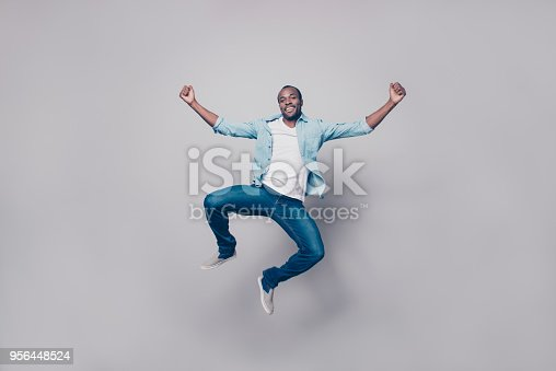 925466128 istock photo Full length, size portrait of confident attractive, joyful, cheerful, positive, glad guy in shirt, sneakers jumping with raised fists, looking at camera, isolated on grey background 956448524