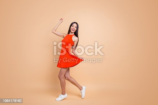 istock Full length size studio photo portrait of beautiful charming good mood toothy beaming smile tender careless carefree cheerful gorgeous korean teen lady holding skirt isolated pastel beige background 1064179162
