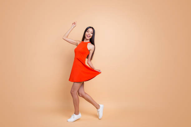 full length size studio photo portrait of beautiful charming good mood toothy beaming smile tender careless carefree cheerful gorgeous korean teen lady holding skirt isolated pastel beige background - sukienka zdjęcia i obrazy z banku zdjęć