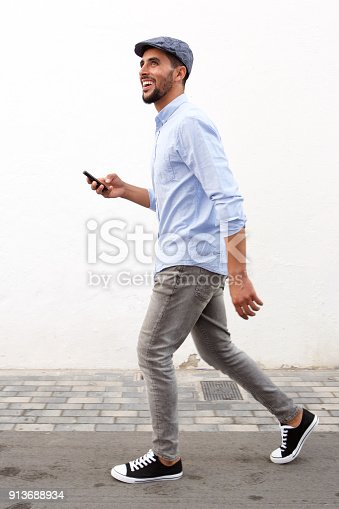 istock Full length smiling man walking with cellphone against white wall 913688934