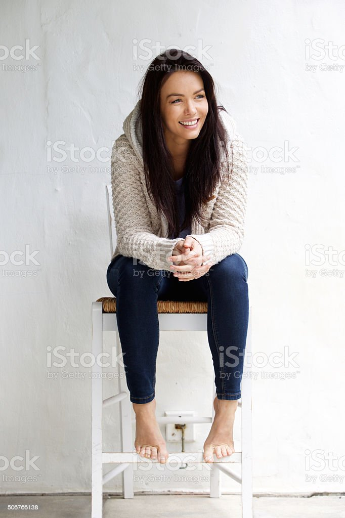 Full length smiling young woman sitting on chair stock photo