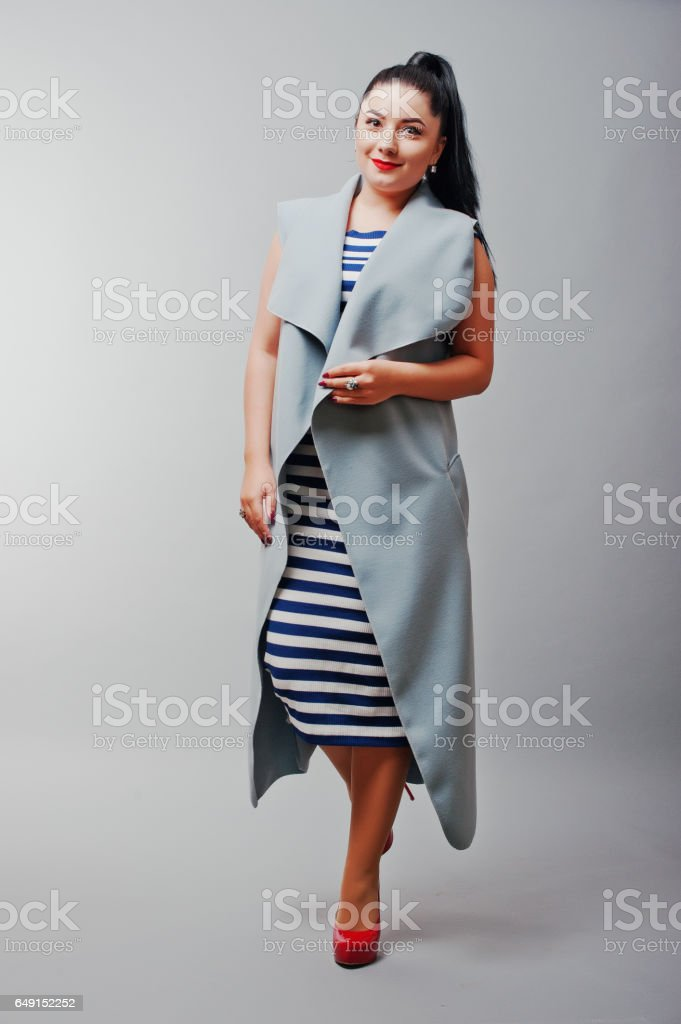Full length studio shot of brunette girl at gray coat, advertisement concept. stock photo