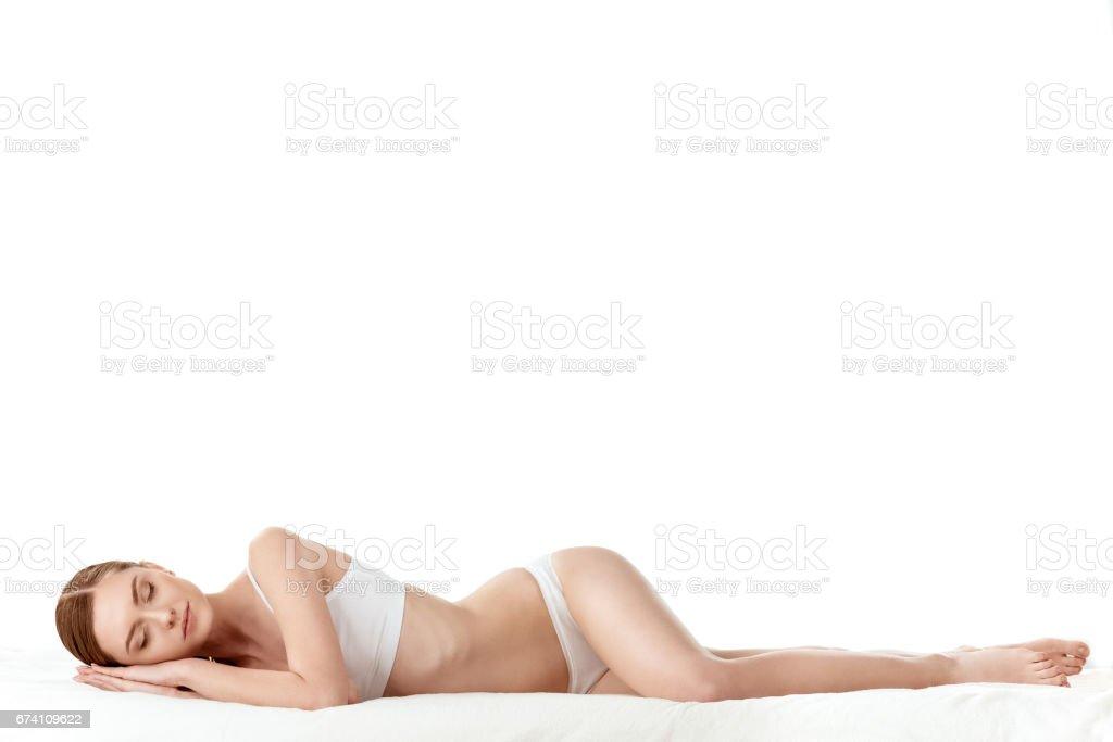 在白色內衣的美麗的年輕婦女的全長看法說謊, 皮膚關心概念 免版稅 stock photo