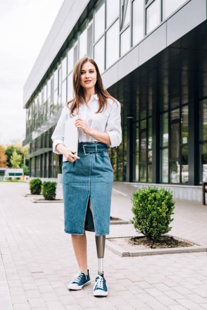 路上でラップトップを保持するデニムスカートの障害のある女性のフルレングスビュー - disabilitycollection ストックフォトと画像