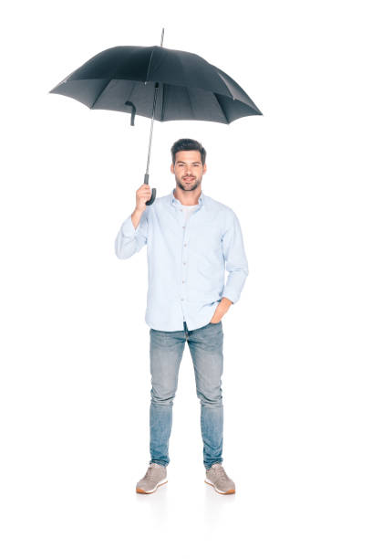full length view of handsome young man holding black umbrella and looking at camera isolated on white - homem chapéu imagens e fotografias de stock