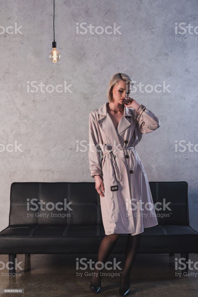 full length view of sexy girl in stockings, high heeled shoes and coat posing indoors stock photo