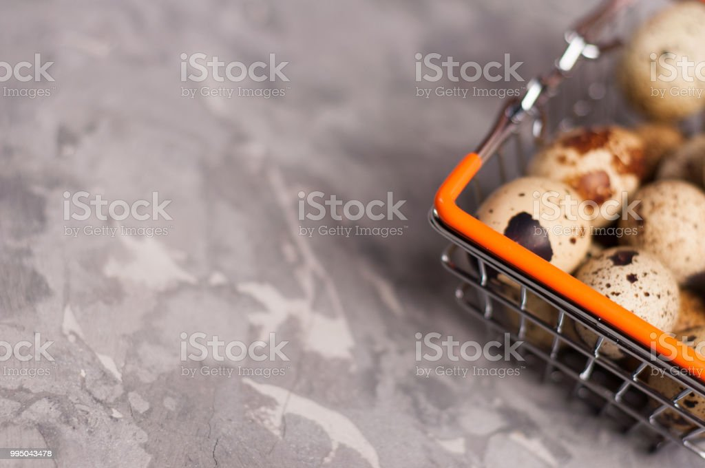 Full metal glossy market basket of spotted fresh quail eggs on old...