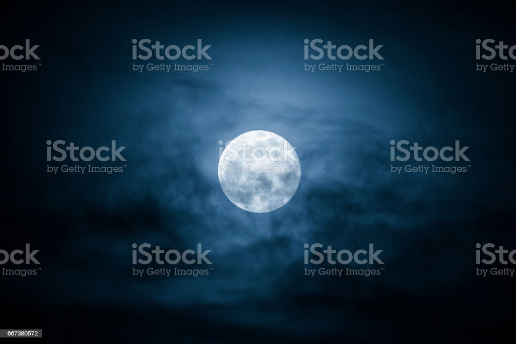 Full Moon and clouds on the night sky stock photo