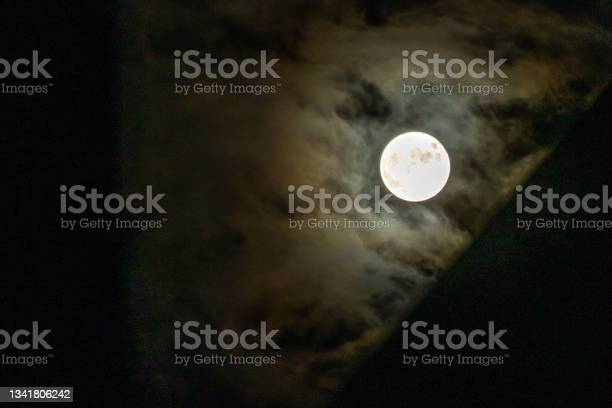 Photo of Full moon covered with thin cloud