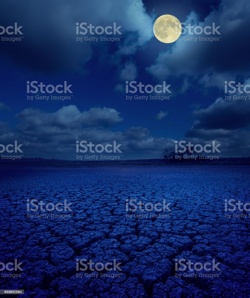 full moon in clouds over cracked earth stock photo