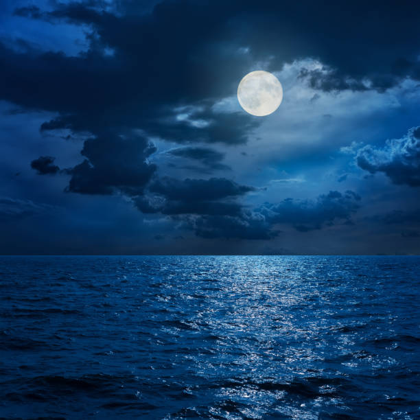 full moon in clouds over sea in night - moon stock pictures, royalty-free photos & images